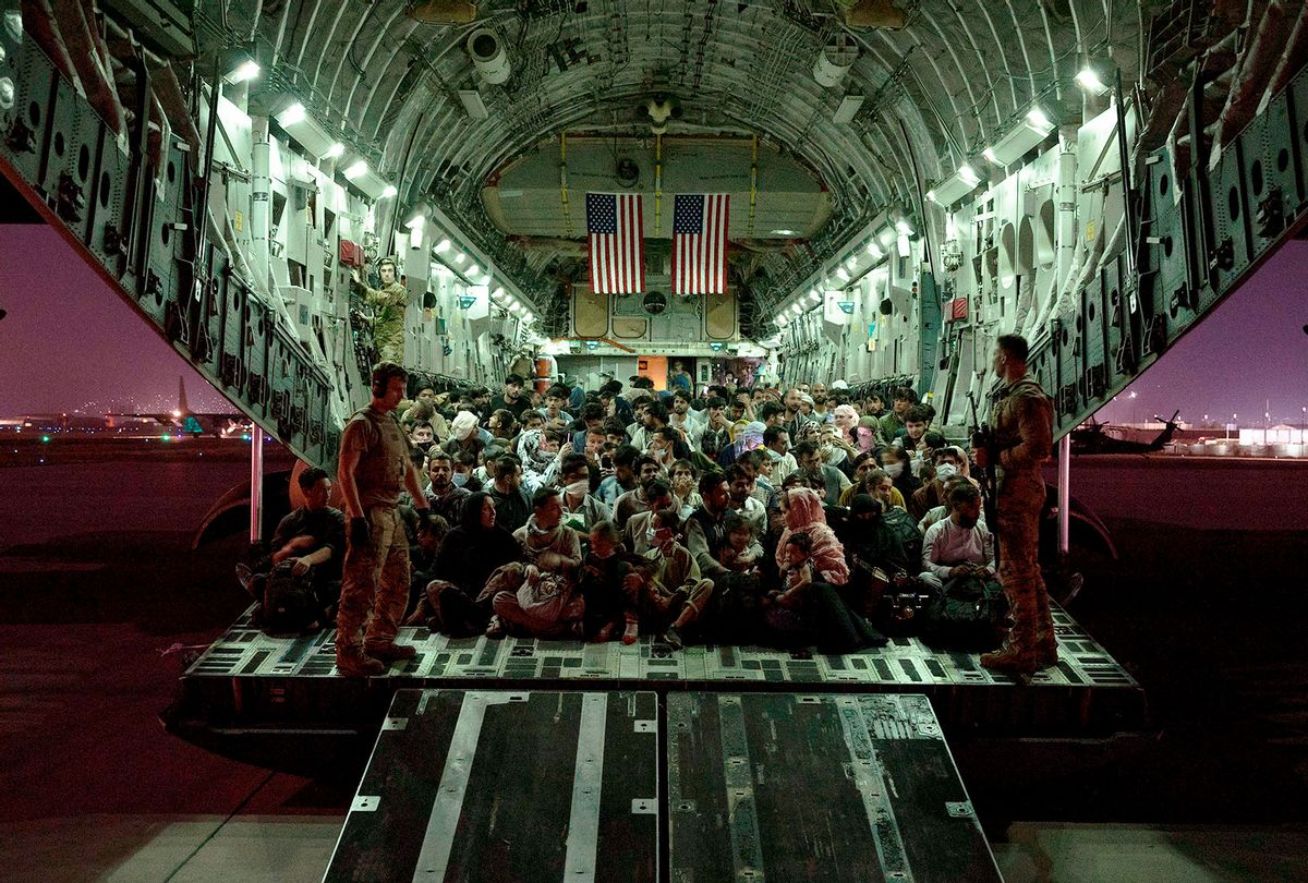 In this handout provided by the U.S. Air Force, an air crew assigned to the 816th Expeditionary Airlift Squadron assists evacuees aboard a C-17 Globemaster III aircraft in support of the Afghanistan evacuation at Hamid Karzai International Airport on August 21, 2021 in Kabul, Afghanistan. (Taylor Crul/U.S. Air Force via Getty Images)