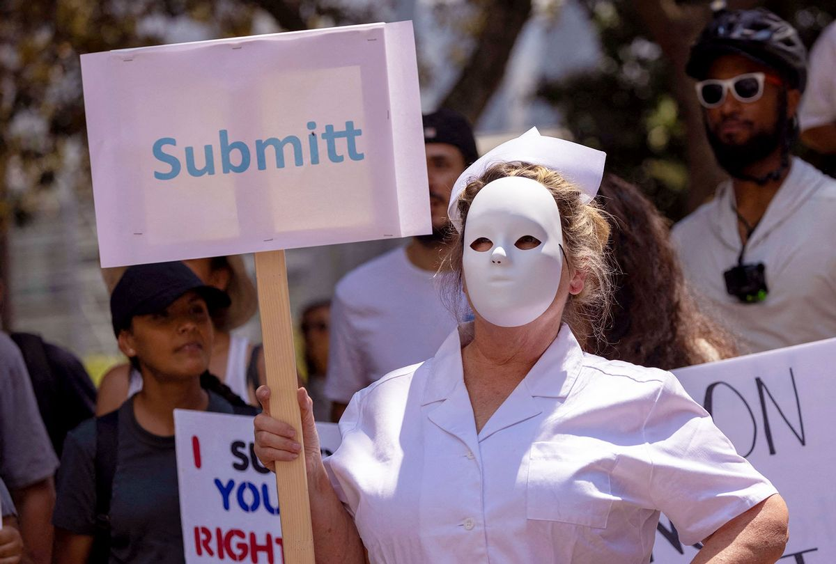 """A protester dressed as a scary nurse holds a mispelled sign that reads """"Submitt"""" at an anti-vaccination protest rally near City Hall, following the Los Angeles City Council's vote earlier this week on drafting an ordinance requiring proof of vaccination to enter many indoor public spaces in Los Angeles, on August 14, 2021. (DAVID MCNEW/AFP via Getty Images)"""