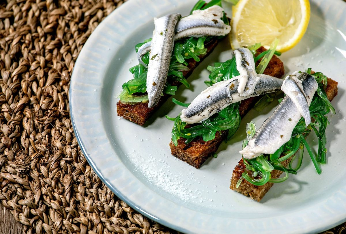 Appetizers tapas pickled anchovies or sardines fillet Wakame seaweed salad on toasted rye bread, served on blue plate with lemon on straw napkin as background. (Natasha Breen/REDA&CO/Universal Images Group via Getty Images)