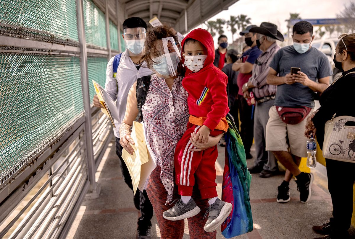 A Honduran mother carries her son, 4, across the U.S.-Mexico border as part of a group of at least 25 asylum seekers who where were allowed to travel from a migrant camp in Mexico into the United States on February 25, 2021 in Matamoros, Mexico (John Moore/Getty Images)