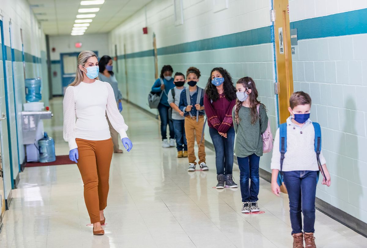 Students and teacher in school during COVID-19 pandemic, wearing masks (Getty Images)