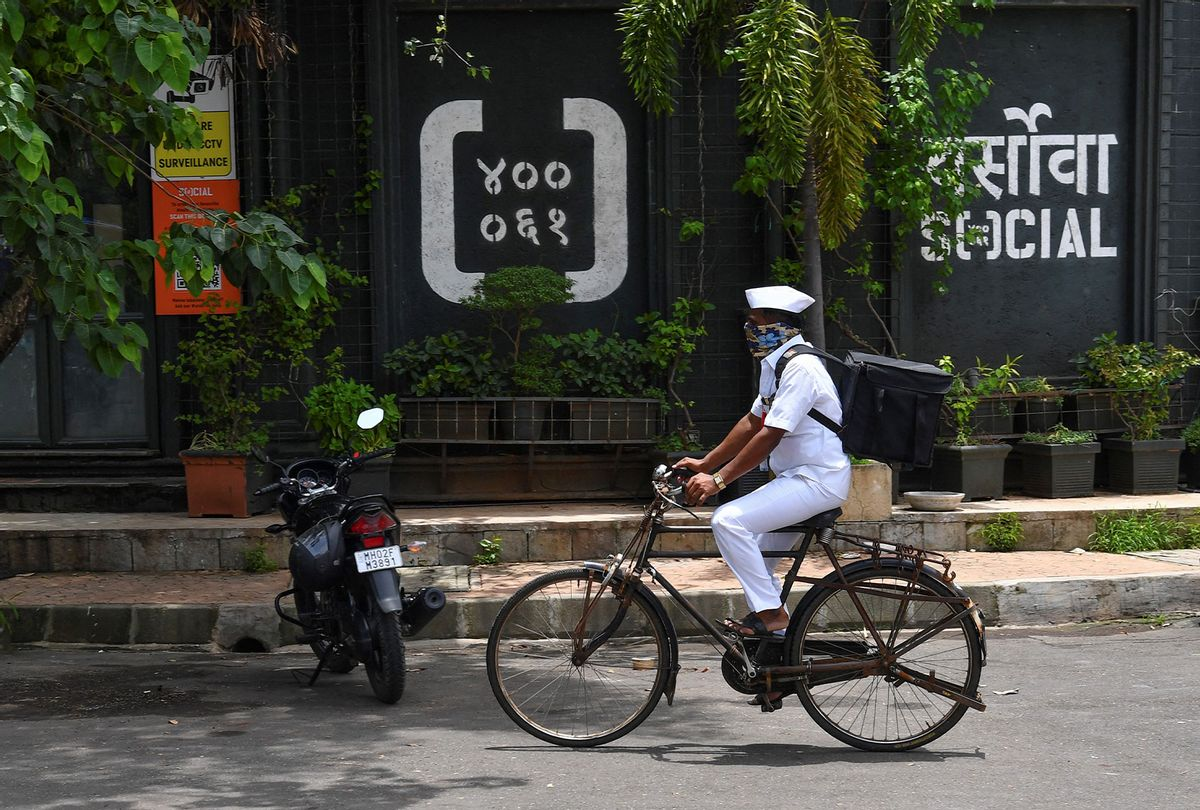 """""""Dabbawala"""", Mumbai's famed cycle-borne tiffin delivery men, Pandurang Jadhav cycles to make a food delivery in Mumbai. - After the pandemic shut offices and put Mumbai's renowned lunchbox deliverymen out of work, the 130-year-old """"Dabbawala"""" network has tied up with a trendy restaurant chain to take on India's billion-dollar start-ups. (INDRANIL MUKHERJEE/AFP via Getty Images)"""