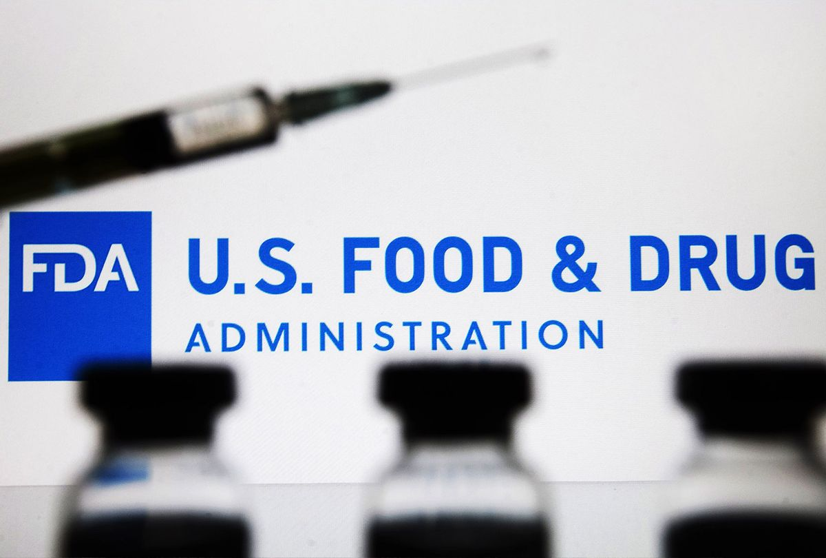 Vials and a medical syringe seen displayed in front of the Food and Drug Administration (FDA) of the United States logo. FDA finds the COVID-19 vaccine. (Photo Illustration by Pavlo Gonchar/SOPA Images/LightRocket via Getty Images)