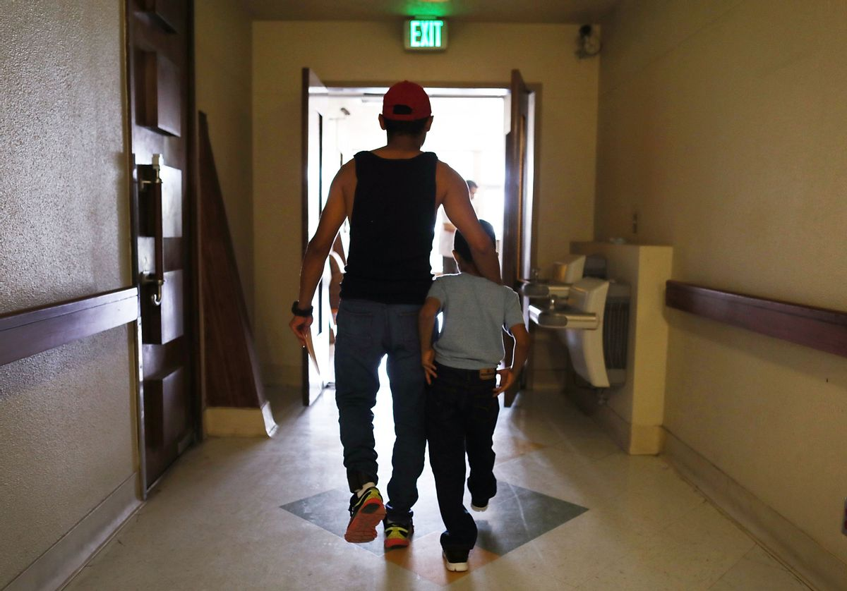 A man walks with his son after being reunited in an I.C.E processing center, after being separated for three months when they tried to cross into the United States. (Joe Raedle/Getty Images)