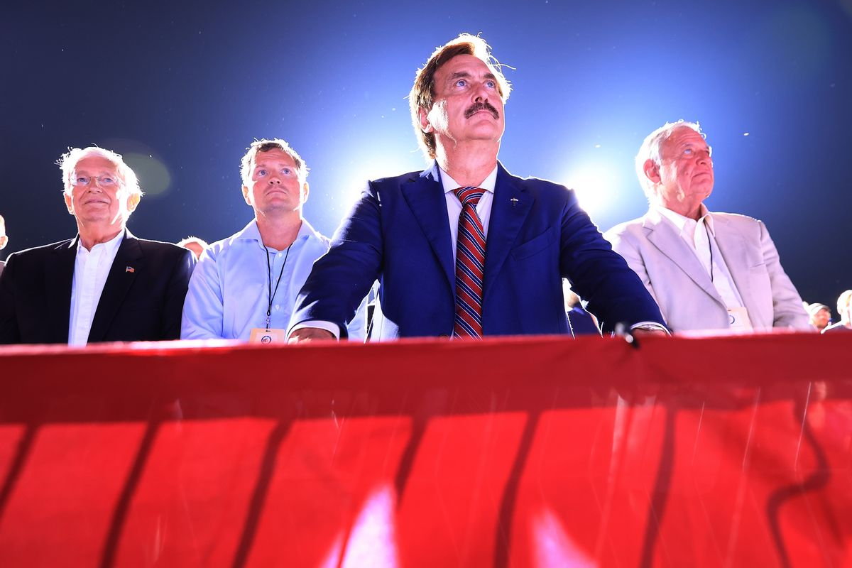 """Founder and CEO of My Pillow, conservative political activist and conspiracy theorist Mike Lindell (C) listens to former U.S. President Donald Trump addresses supporters during a """"Save America"""" rally at York Family Farms on August 21, 2021 in Cullman, Alabama. (Chip Somodevilla/Getty Images)"""