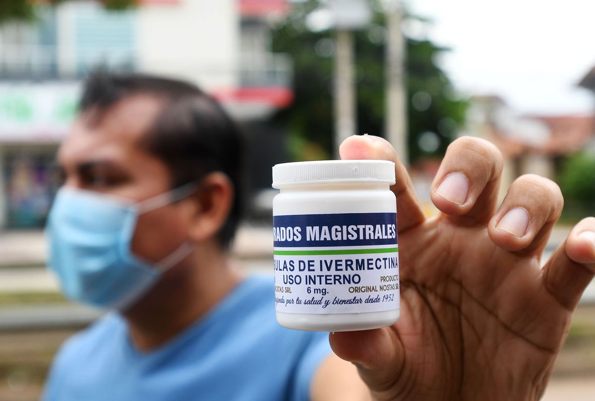 A man with a mouth guard shows a can of ivermectin capsules as he comes out of the pharmacy. (Rodrigo Urzagasti/picture alliance via Getty Images)