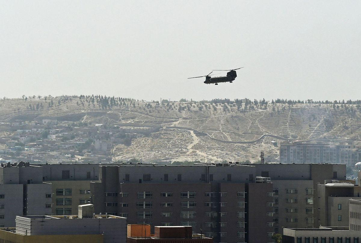 A U.S. Chinook military helicopter flies above the US embassy in Kabul on August 15, 2021. Several hundred employees of the US embassy in Kabul have been evacuated from Afghanistan, a US defense official said on August 15, 2021, as the Taliban entered the capital. (WAKIL KOHSAR/AFP via Getty Images)