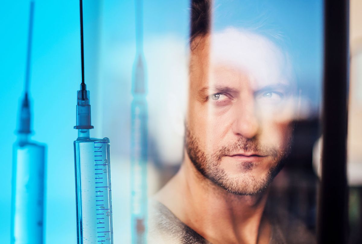 Close-up of man looking through window seen through glass | Vaccines (Photo illustration by Salon/Getty Images)