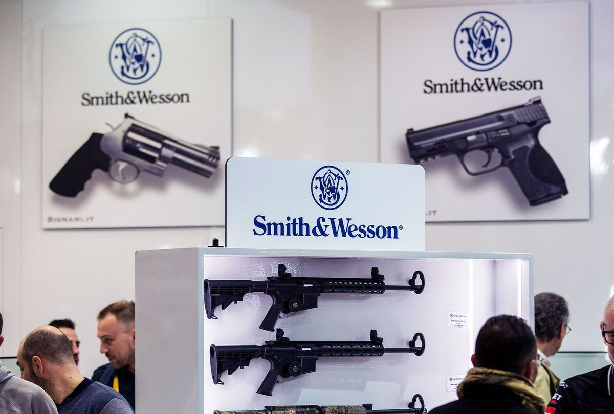 Fairgoers are pictured in front of the Smith & Wesson display stand  (Emanuele Cremaschi/Getty Images)