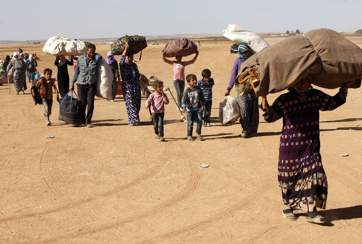 Syrian Kurdish refugees walk with their belongings after crossing into Turkey from the Syrian border town of Kobani on September 26, 2014 near the southeastern town of Suruc in Sanliurfa province, Turkey. (Stringer/Getty Images)