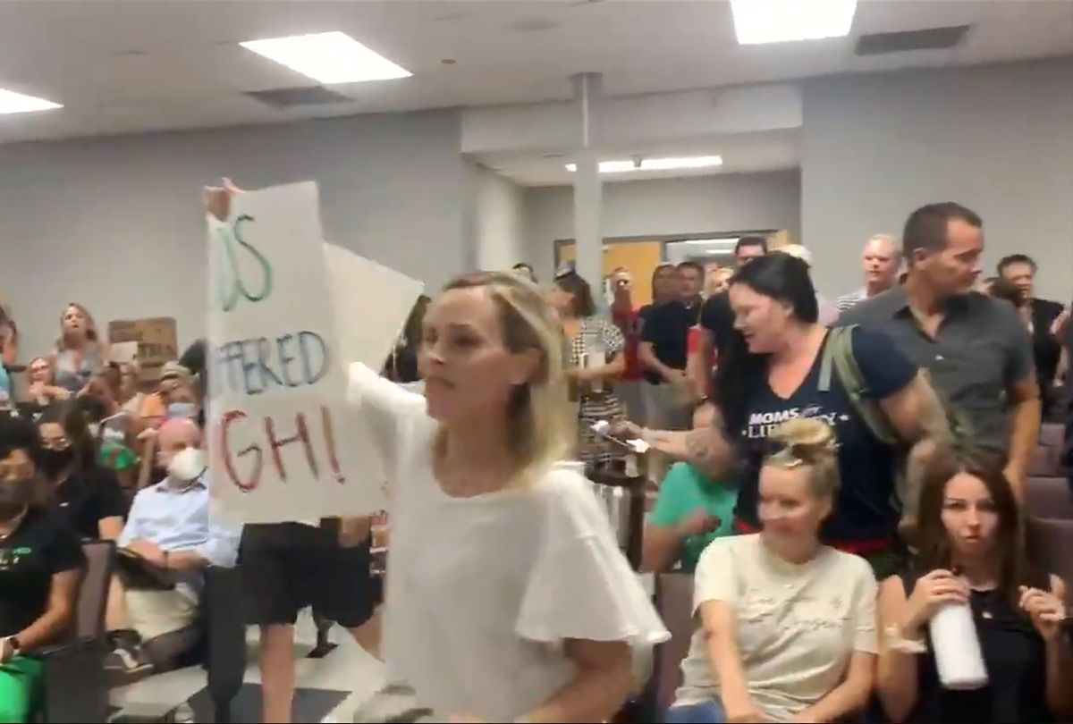 Dozens of enraged anti-mask parents followed an unruly man out in a mob at the Williamson County Schools meeting, Tennessee. (Twitter/@brinleyhineman)
