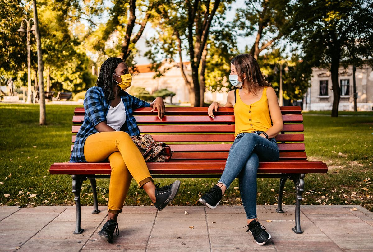Two women with protective face masks on sitting on park bench with social distance between. (Getty Images)