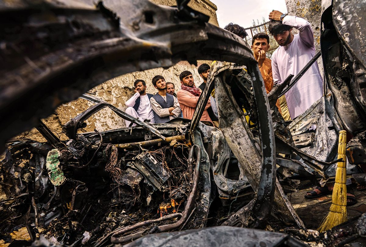 Relatives and neighbors of the Ahmadi family gathered around the incinerated husk of a vehicle targeted and hit earlier Sunday afternoon by an American drone strike, in Kabul, Afghanistan, Monday, Aug. 30, 2021. (Getty Images/MARCUS YAM/LOS ANGELES TIMES)
