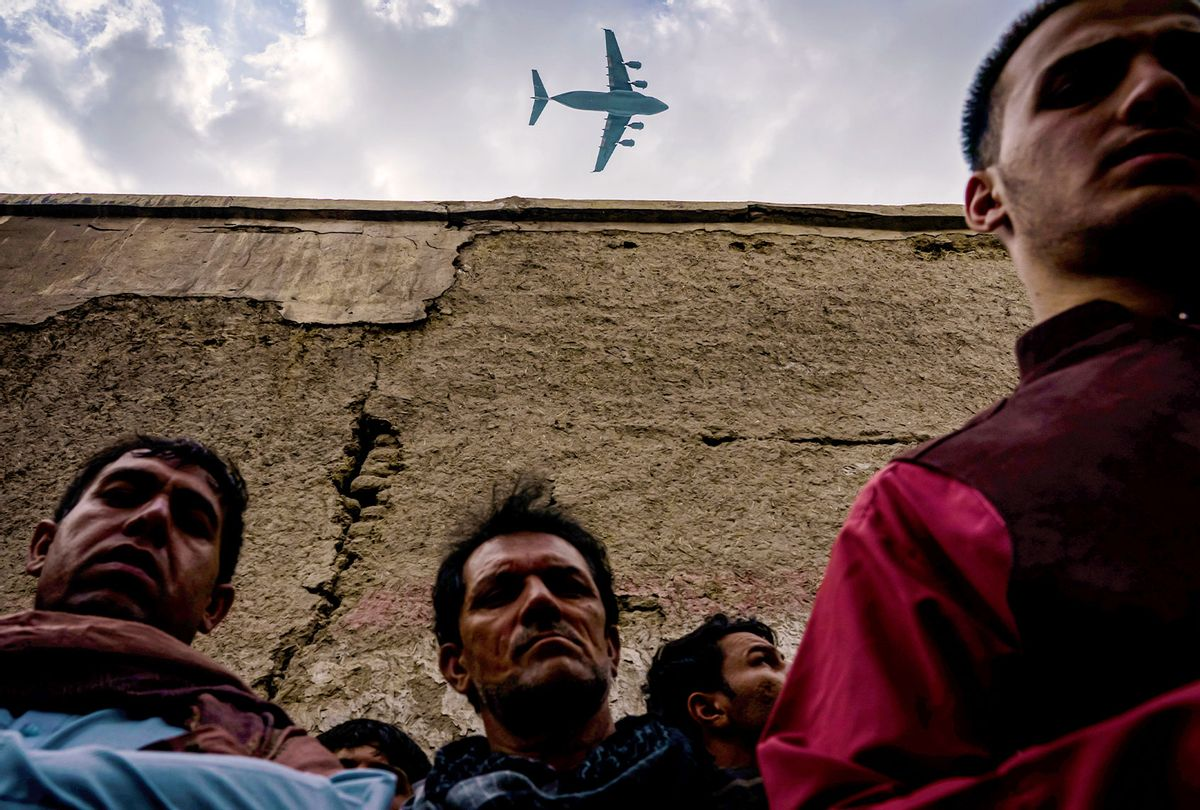 A military transport plane flies over as Relatives and neighbors of the Ahmadi family gathered around the incinerated husk of a vehicle targeted and hit earlier Sunday afternoon by an American drone strike, in Kabul, Afghanistan, Monday, Aug. 30, 2021. ( (Getty Images/MARCUS YAM/LOS ANGELES TIMES)