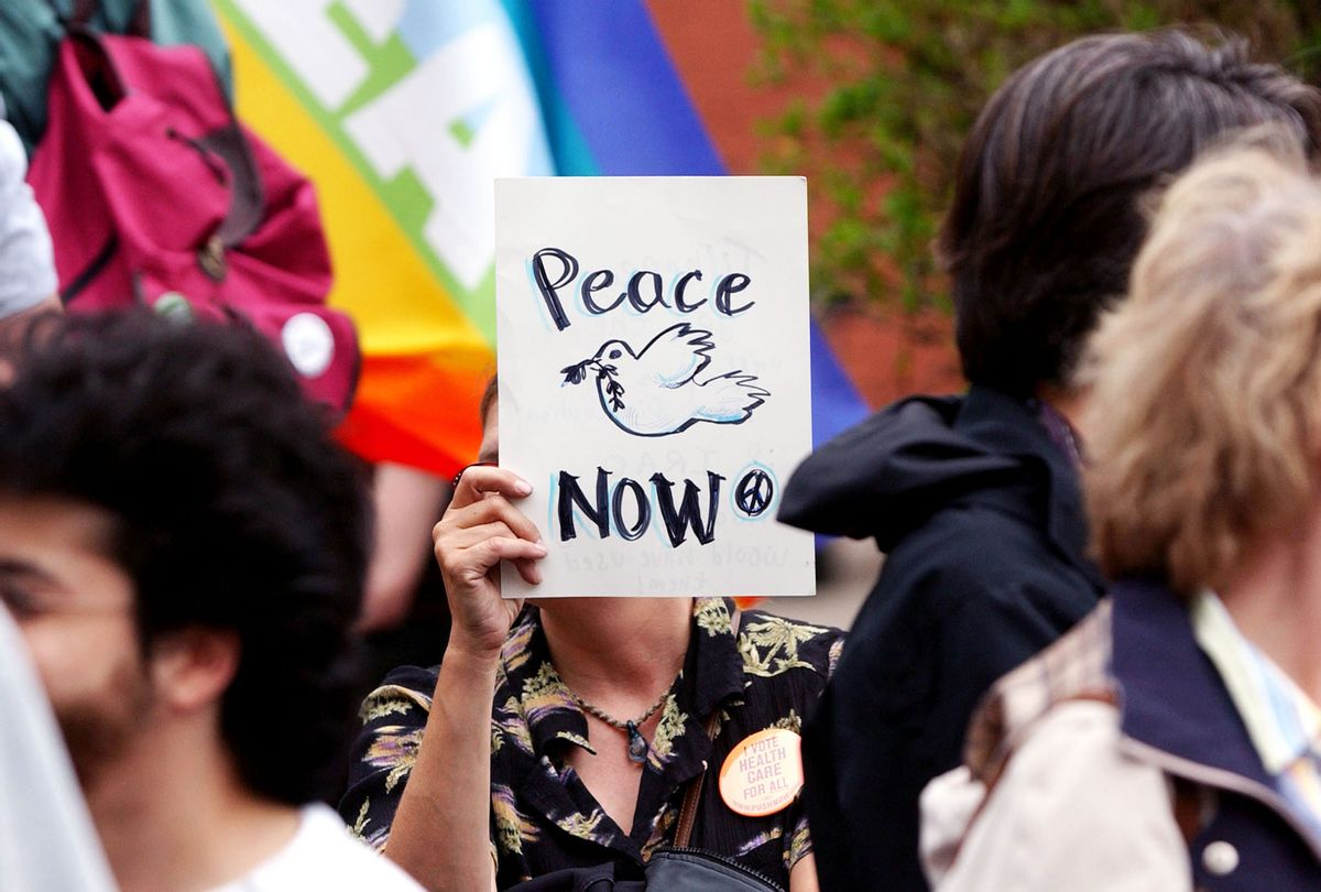 A peace activist holds a peace sign (Jeff Swensen/Getty Images)