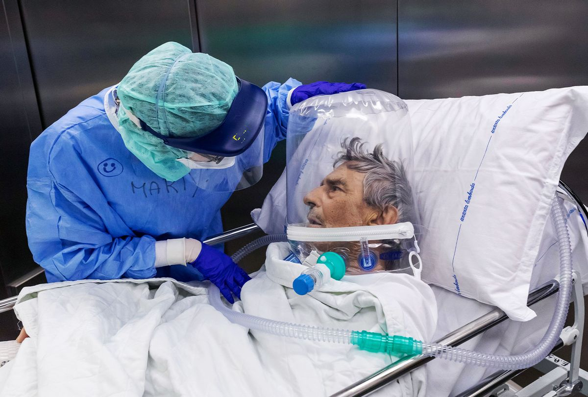 A nurse attends to a COVID-19 patient that is wearing a CPAP helmet while he is moved out of the Intensive Care Unit (ICU) of the Pope John XXIII Hospital on April 7, 2020 in Bergamo, Italy. (Marco Di Lauro/Getty Images)