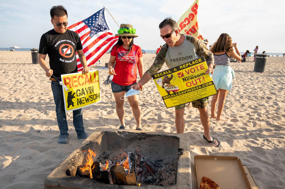 Protesters burn face masks at Huntington City Beach in Huntington Beach, California, on June 15, 2021, as part of a protest against California Gov. Gavin Newsom and the state's mask mandates. (Leonard Ortiz/MediaNews Group/Orange County Register via Getty Images)