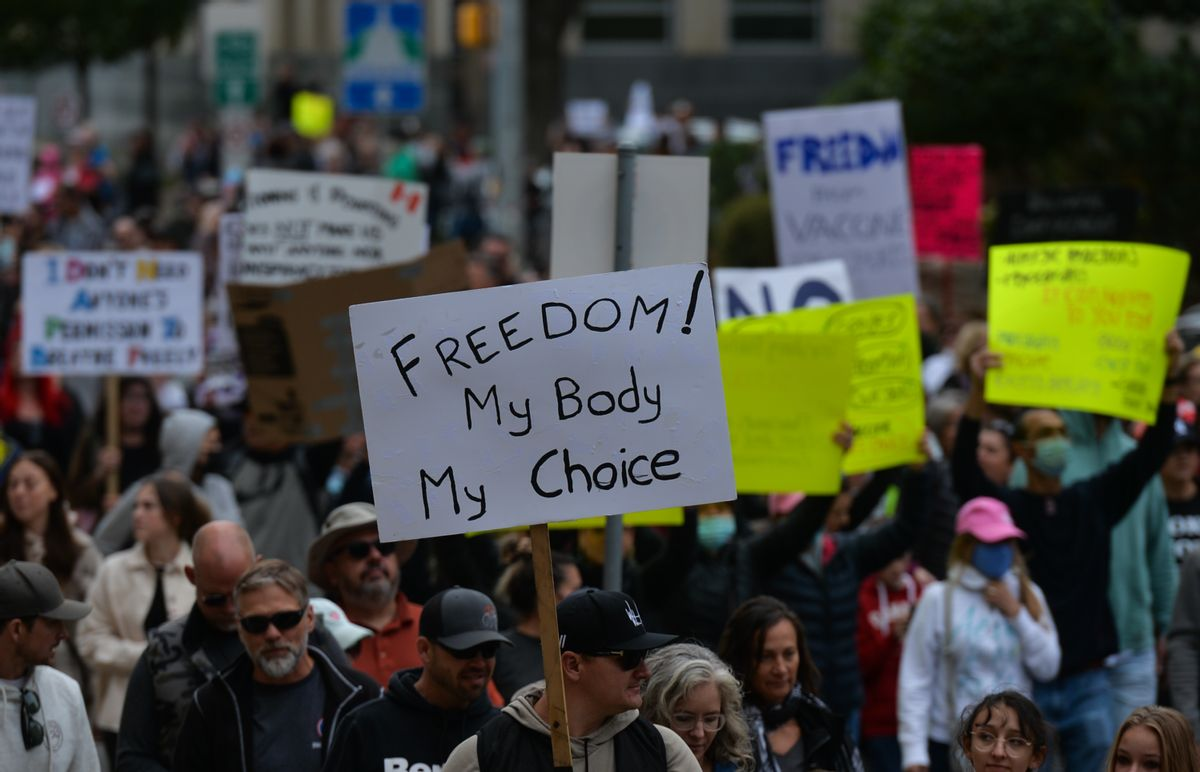 """Anti-vaccine protesters hold signs, including one which reads """"Freedom! My body, my choice."""" (Getty Images)"""