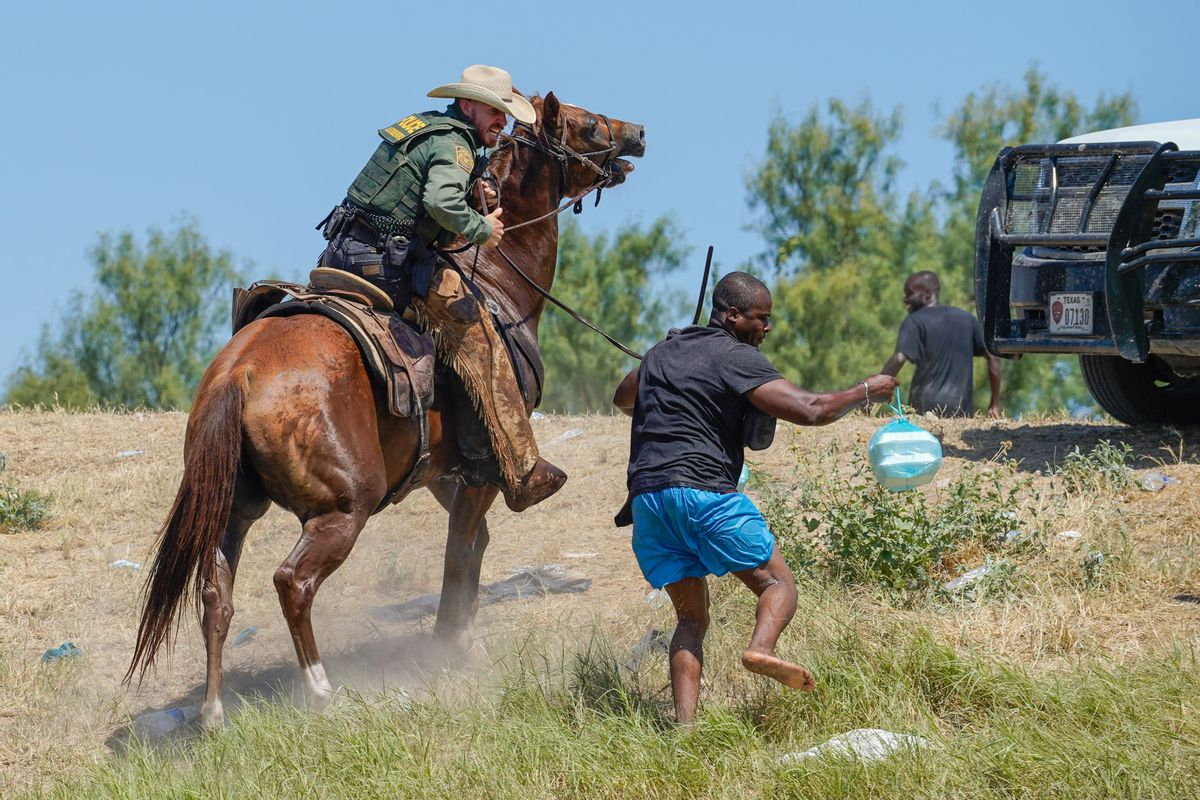 A United States Border Patrol agent on horseback uses the reins to try and stop a Haitian migrant from entering an encampment on the banks of the Rio Grande near the Acuna Del Rio International Bridge in Del Rio, Texas on September 19, 2021.  (PAUL RATJE/AFP via Getty Images)