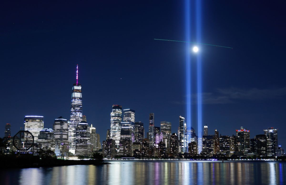 A passing helicopter creates a cross through the beams of the Tribute in Light as it is tested over lower Manhattan and One World Trade Center in New York City. (Gary Hershorn/Getty Images)