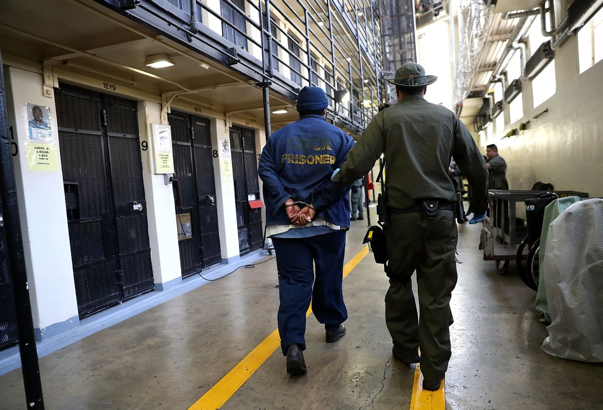 An armed California Department of Corrections and Rehabilitation (CDCR) officer escorts a condemned inamte at San Quentin State Prison's death row. (Justin Sullivan/Getty Images)