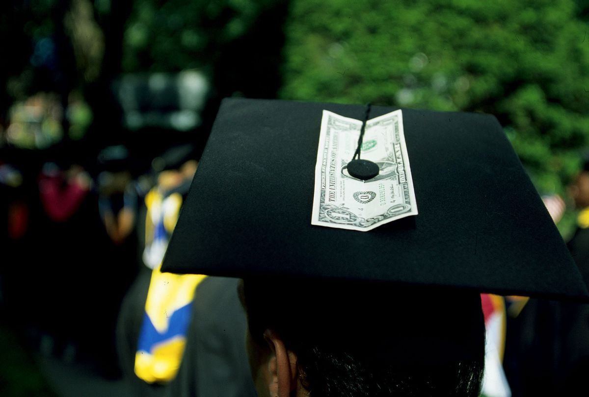 A student with a dollar bill attached to his cap during the graduation ceremony. (Brooks Kraft LLC/Corbis via Getty Images)