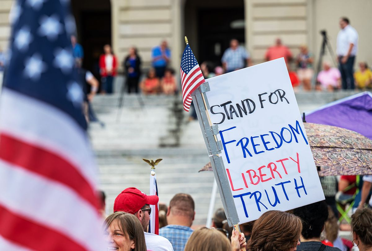 People display signs during the Kentucky Freedom Rally at the capitol building on August 28, 2021 in Frankfort, Kentucky. (Jon Cherry/Getty Images)