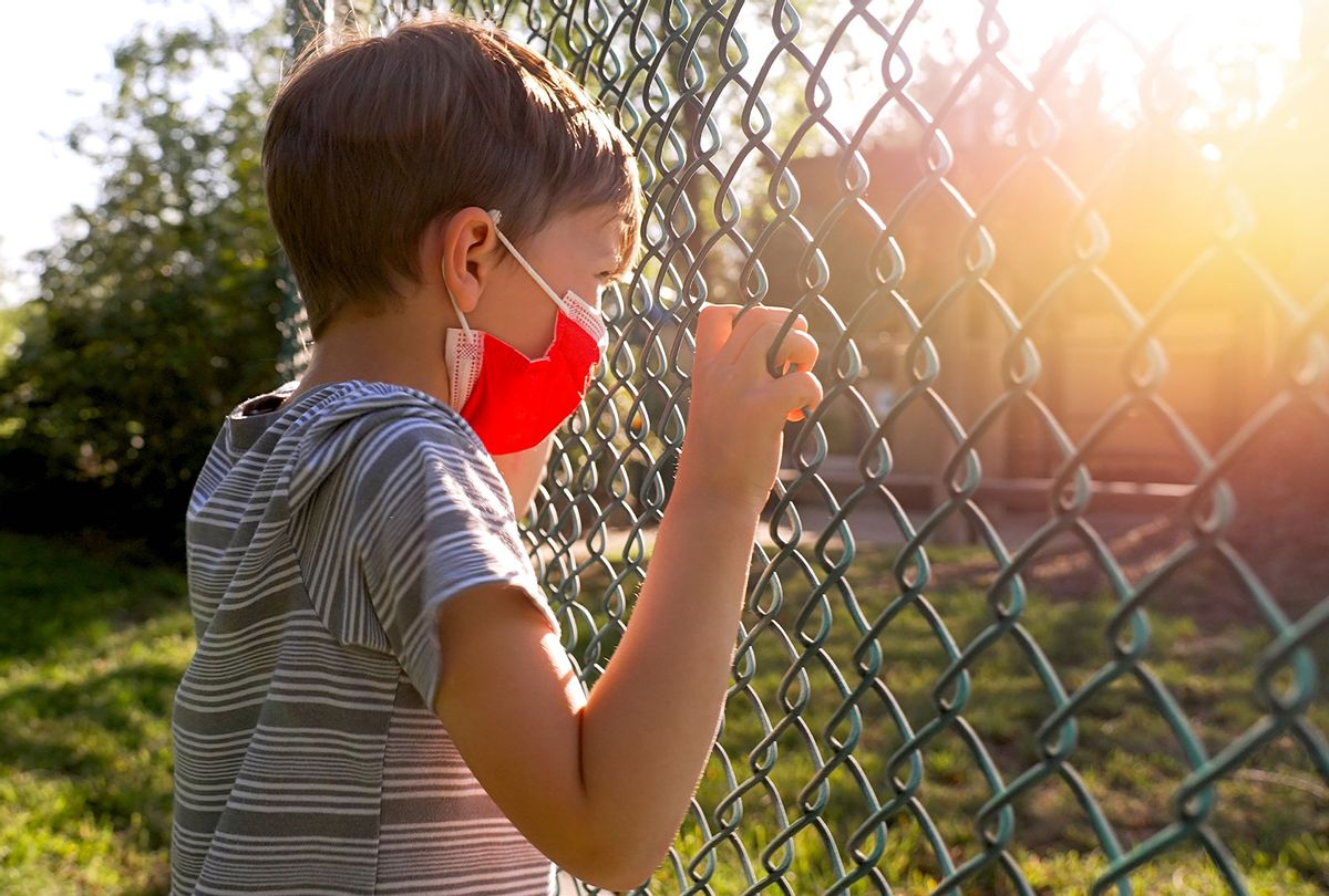 Serious upset little boy wearing a protective face mask looking through a school fence shaking it (Getty Images/Juanmonino)