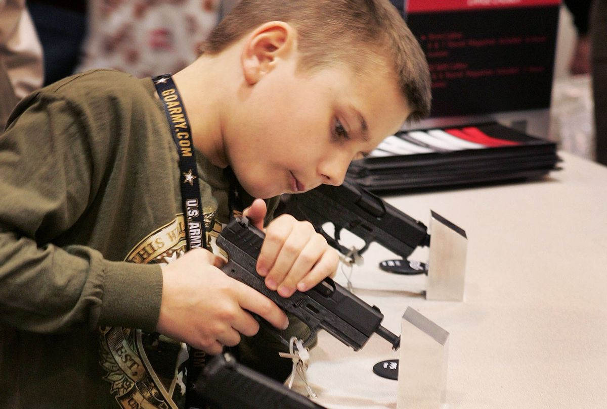 Eight-year-old Dakota Stevenson looks over Walthers pistols at the Smith & Wesson booth during the 136th NRA Annual Meetings and Exhibits April 13, 2007 in St. Louis, Missouri. (Scott Olson/Getty Images)