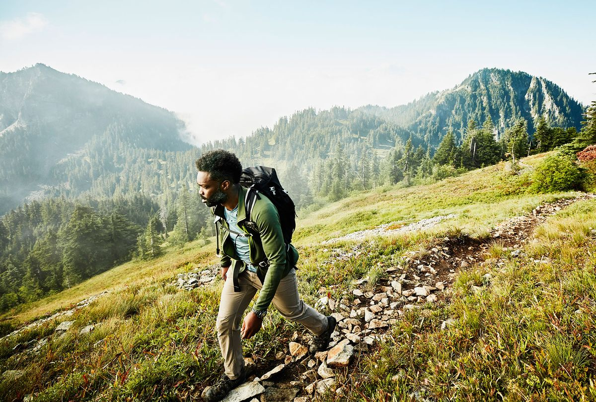 Man on early morning hike up mountainside (Getty Images/Thomas Barwick)