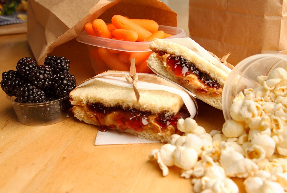 A peanut butter and jelly sandwich surrounded by several other food items that would make up a child's lunch. (Getty Images/steele2123)