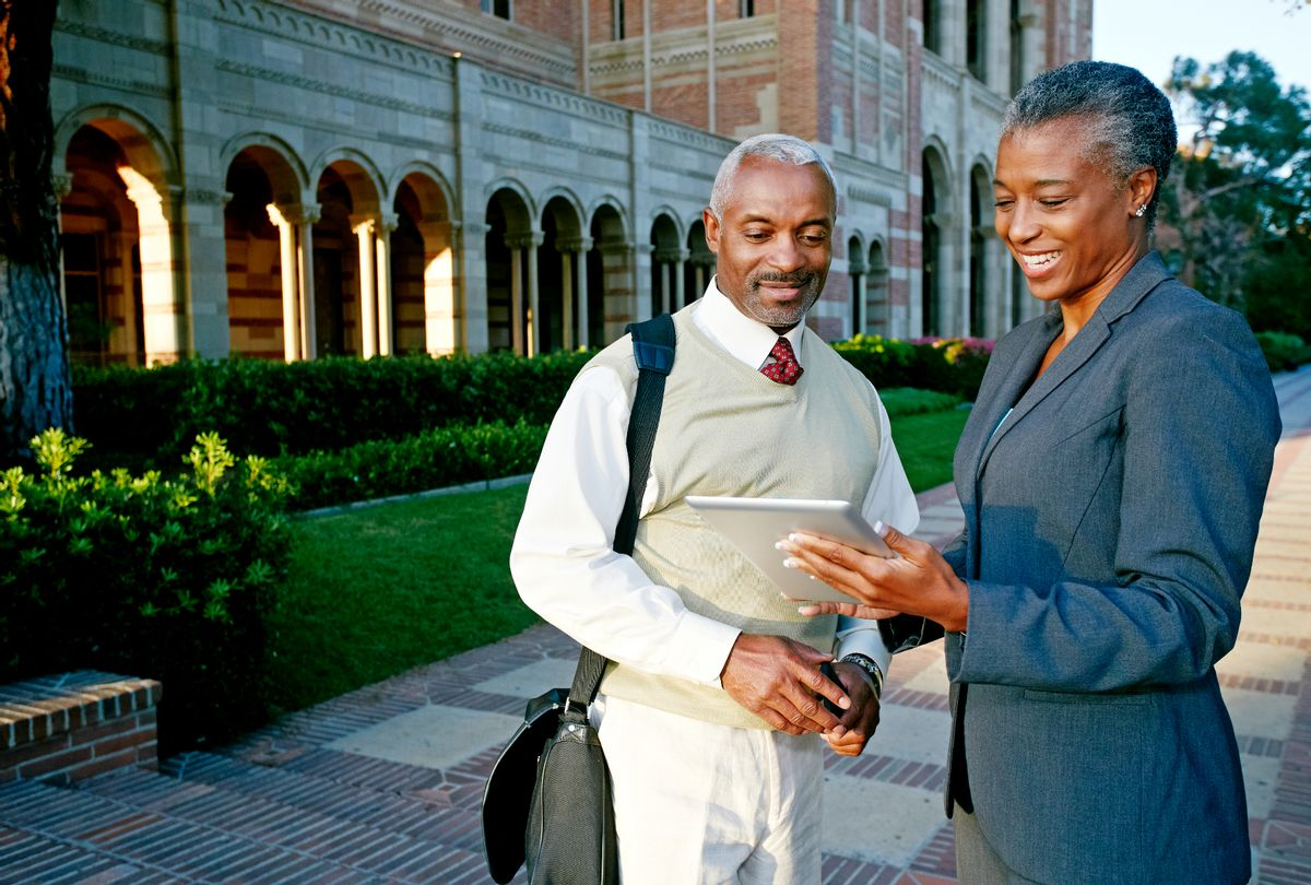 Professors on campus looking at a tablet (Getty stock photos)