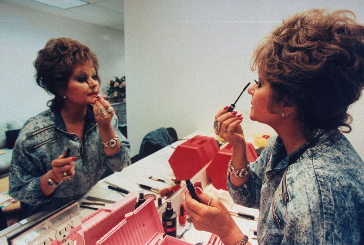 TV talk show host Tammy Faye Bakker Messner applying mascara to eyelashes in mirror in dressing room (John Storey/Getty Images)