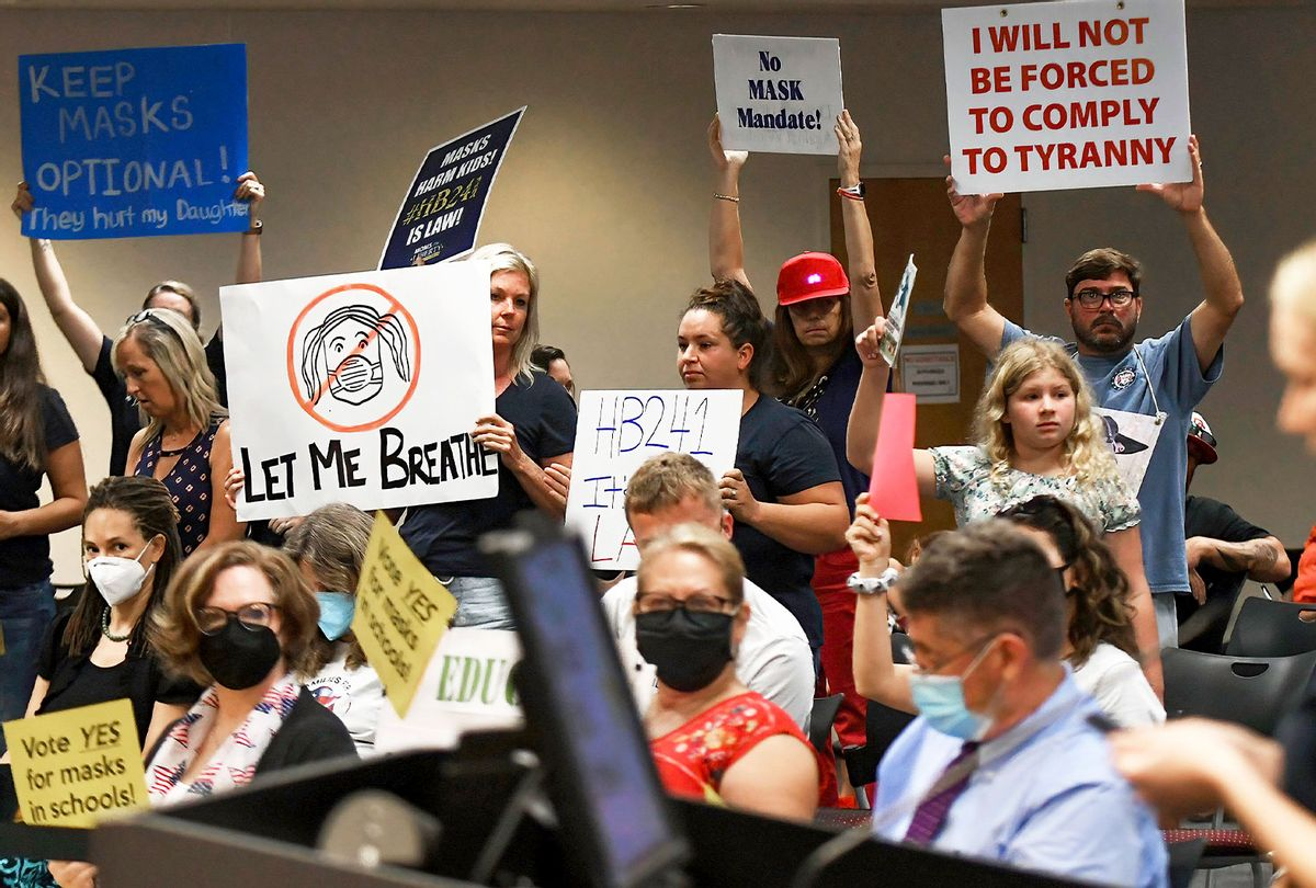 People demonstrate with placards at an emergency meeting of the Brevard County, Florida School Board in Viera to discuss whether face masks in local schools should be mandatory. An executive order signed by Florida Governor Ron DeSantis banning mask mandates in schools was thrown out by a Florida judge on Friday. (Paul Hennessy/SOPA Images/LightRocket via Getty Images)