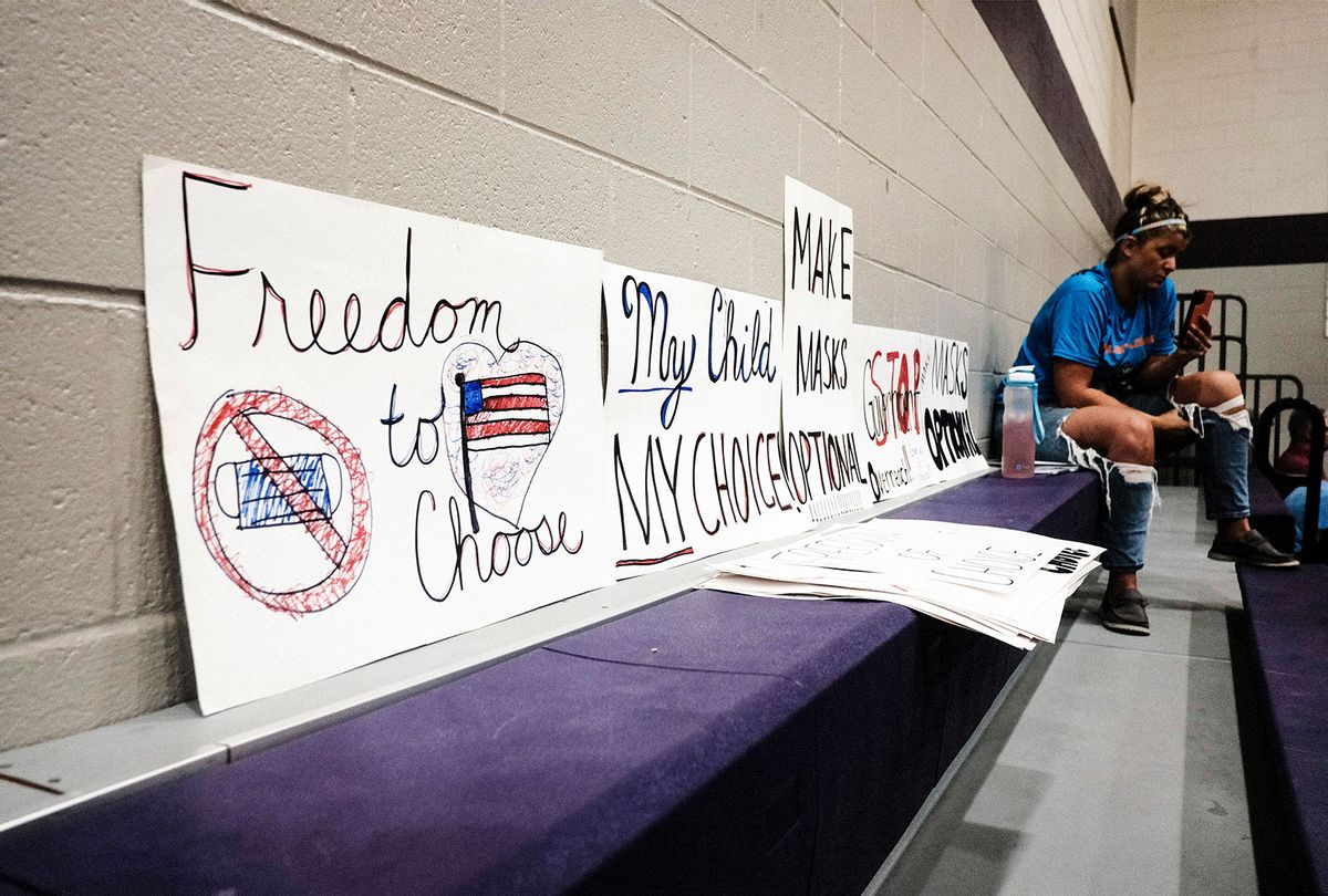 An attendee sits next to anti-vaccine mandate signs at a special Board of Education Meeting on mask mandates for students and staff in Kalamazoo County Schools at the Schoolcraft High School Gymnasium on August 23, 2021 in Schoolcraft, Michigan. The Schoolcraft Local School District opened the floor for public discussion. (Matthew Hatcher/Getty Images)