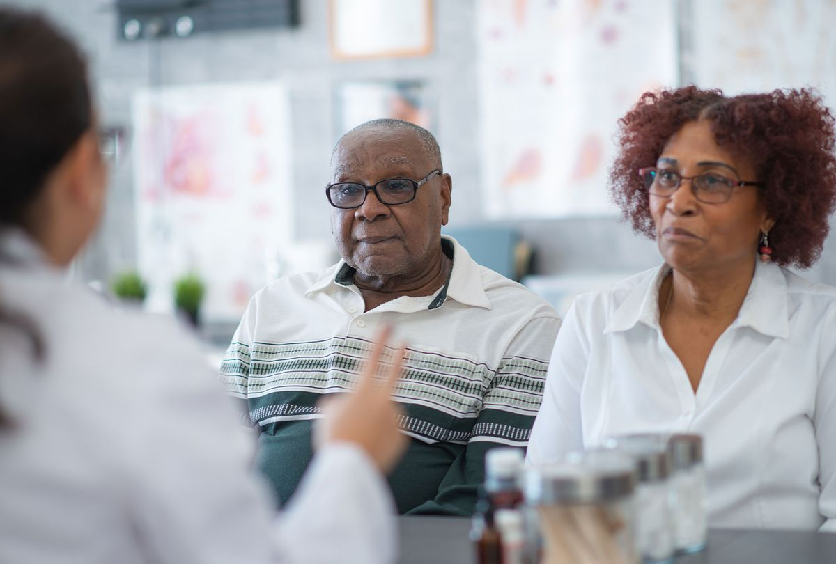 A couple sit next to each other in a doctor's office and listen carefully to their doctor. (Getty Images/FatCamera)