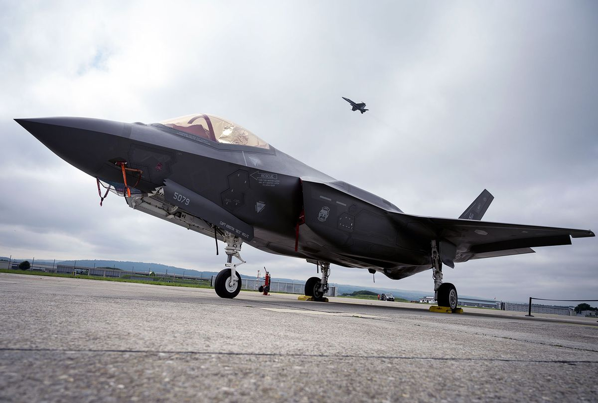 A Lockheed Martin F-35 Lightning II fighter jet is parked on the tarmac at the Payerne Air Base as a Boeing McDonnell Douglas F/A-18 Hornet takes off in the background, during flight and ground tests, as Switzerland is looking for a new fighter jet to replace its aging fleet, on June 7, 2019 in Payerne. (FABRICE COFFRINI/AFP via Getty Images)