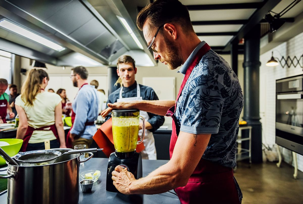 Man in cooking class mixing food in blender (Getty Images/Hinterhaus Productions)