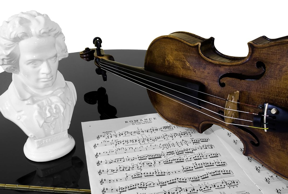 A violin, score, and bust of Beethoven atop a piano, isolated against a white background (Getty Images/davidcrehner)