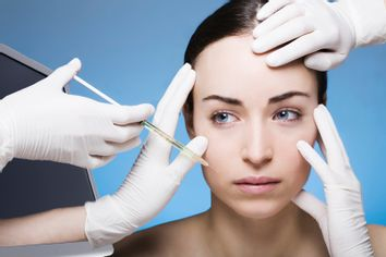 young woman gets a botox injection into the skin