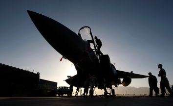Members of the ground crew work on U.S. Air Force F-15E fighter jet following a mission over Afghanistan at Bagram air base