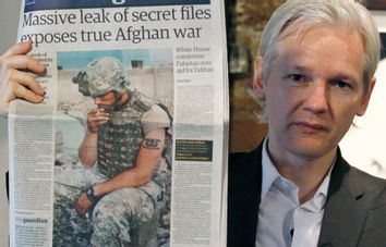 Wikileaks founder Julian Assange holds up a copy of a newspaper during a press conference at the Frontline Club in central London