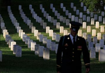 An honor guard taking part in a wreath laying ceremony  walks past the gravestones at Arlington National Cemetery outside Washington