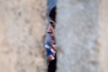 A Palestinian woman waits behind a wall after she was refused entry to cross into Jerusalem from Israel's Qalandiya checkpoint outside Ramallah