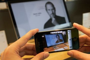 A man uses his iPhone to photograph image of Steve Jobs