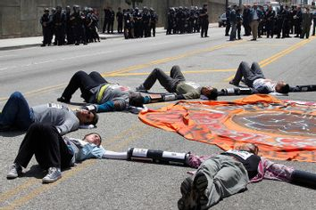 Protesters against Arizona's new law SB 1070 lie on a street with their hands linked together