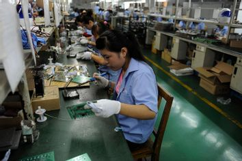 An employee works on circuit boards at an electronic component factory in Hefei, Anhui province, China.