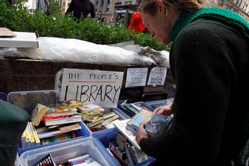 A demonstrator browses books at the library of the Occupy Wall Street protesters' camp at Zuccotti Park in lower Manhattan in New York October 3, 2011.