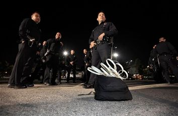 Los Angeles Police department officer wait to board buses before they evict protesters from the Occupy LA encampment outside City Hall in Los Angeles