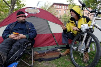 Protesters who gave their names as Trev H., left, and Philippe D'Orlando, right, both homeless, talk outside a tent in a Burnside Park where Occupy Providence protesters are camping in downtown Providence, R.I.